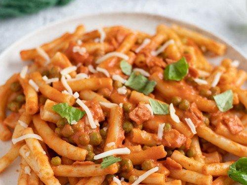Maccheroni mit Erbsen und Schinken in Tomatensoße und Sahne